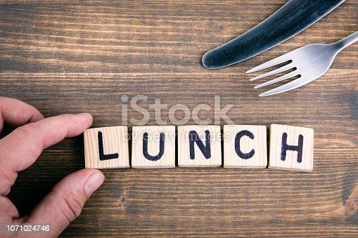 Lunch. Wooden letters on the office desk, informative and communication background