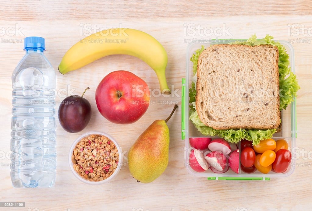 Lunchbox with a sandwich, fruits, vegetables, and water stock photo