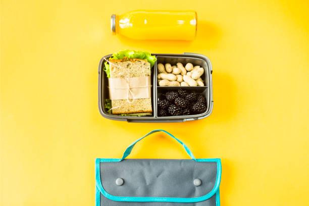 matlåda med mat - en smörgås, bär och nötter - bredvid en flaska apelsinjuice och en väska för en lunch. mat kan du ta med dig. ovanifrån, platt låg, - lunchlåda bildbanksfoton och bilder