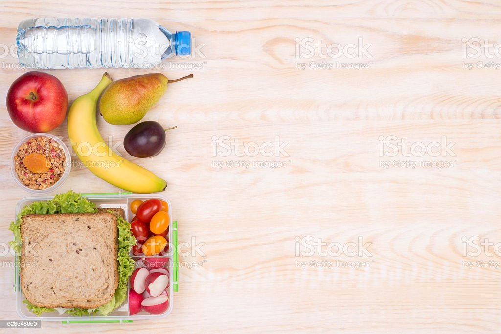 Lunchbox with sandwich, fruits, vegetables and water stock photo