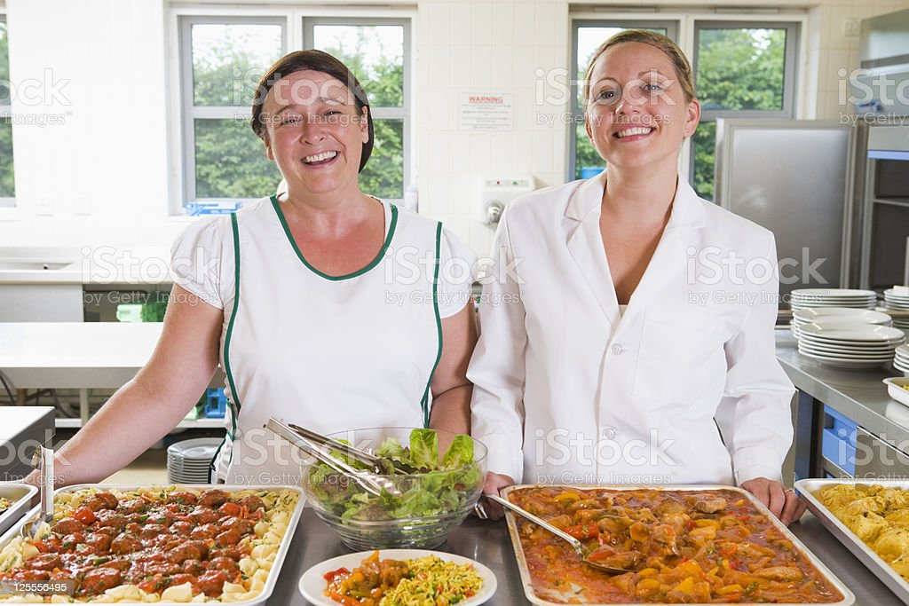 Lunchladies beside trays of food in school cafeteria stock photo