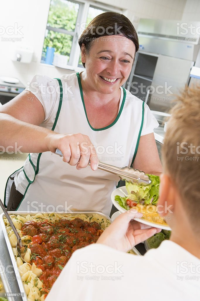 Lunchlady serving plate of food in school cafeteria stock photo