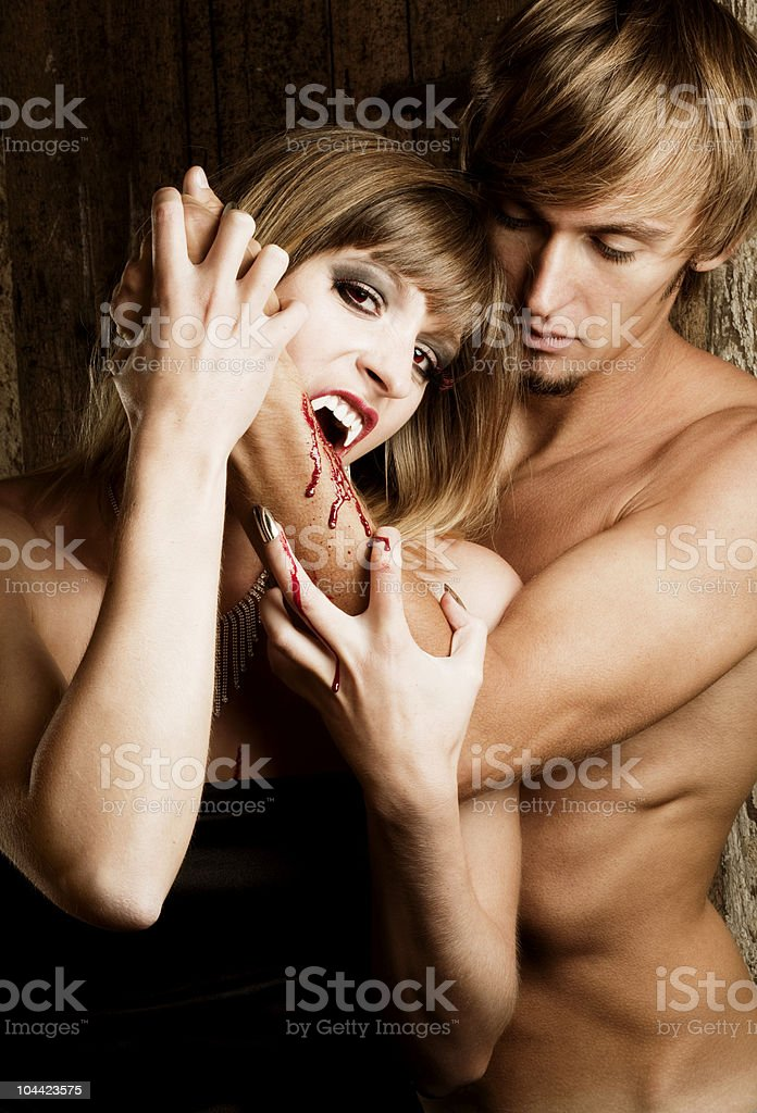 Lunchtime: Female Vampire is biting a male human stock photo