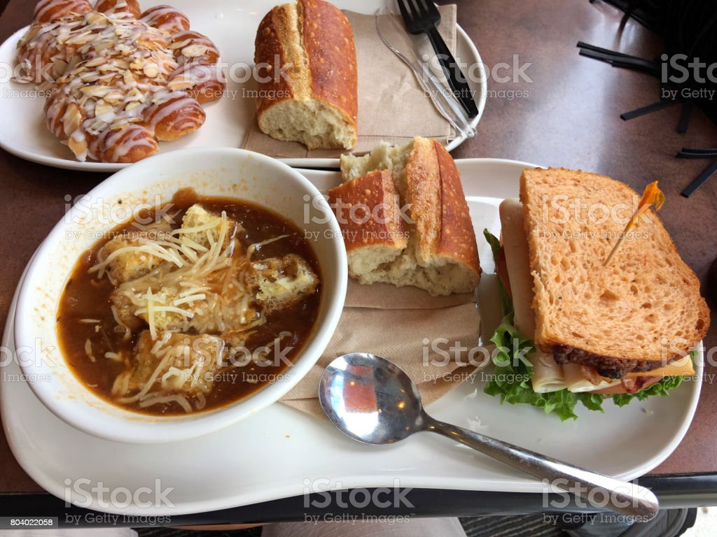 Lunchtime meal of Bistro French Onion Soup, Turkey Bravo sandwich, french bread and a bearclaw pastry stock photo