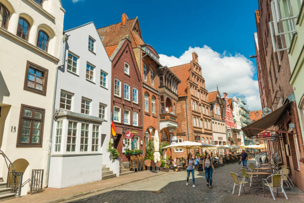Luneburg, Germany: Old historical houses in one of the streets of the famous German town. Traditional architecture style, brick and painted buildings with triangle roofs Luneburg (Lüneburg) - July 2018, Germany: Old historical houses in one of the streets of the famous German town. Traditional architecture style, brick and painted buildings with triangle roofs lüneburg stock pictures, royalty-free photos & images