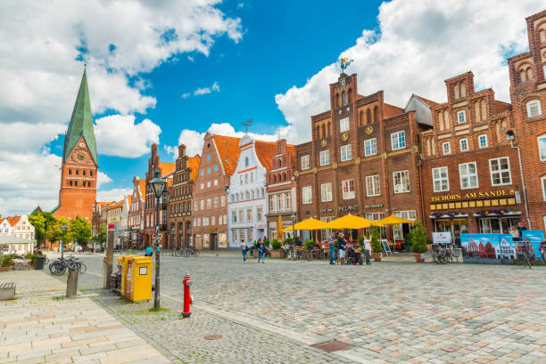 Luneburg, Germany: View of the central street with old brick houses, bar, cafe, shops and walking people Luneburg - July 2018, Germany: View of the central street with old brick houses, bar, cafe, shops and walking people lüneburg stock pictures, royalty-free photos & images