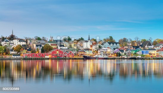 Panoramic view of illuminated waterfront of Lunenburg reflecting in the harbour. Lunenburg, Nova Scotia, Canada.