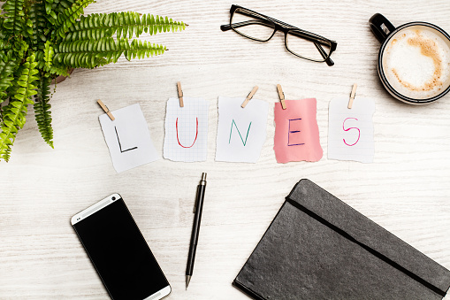 Lunes sign and a coffe on a desk (monday)