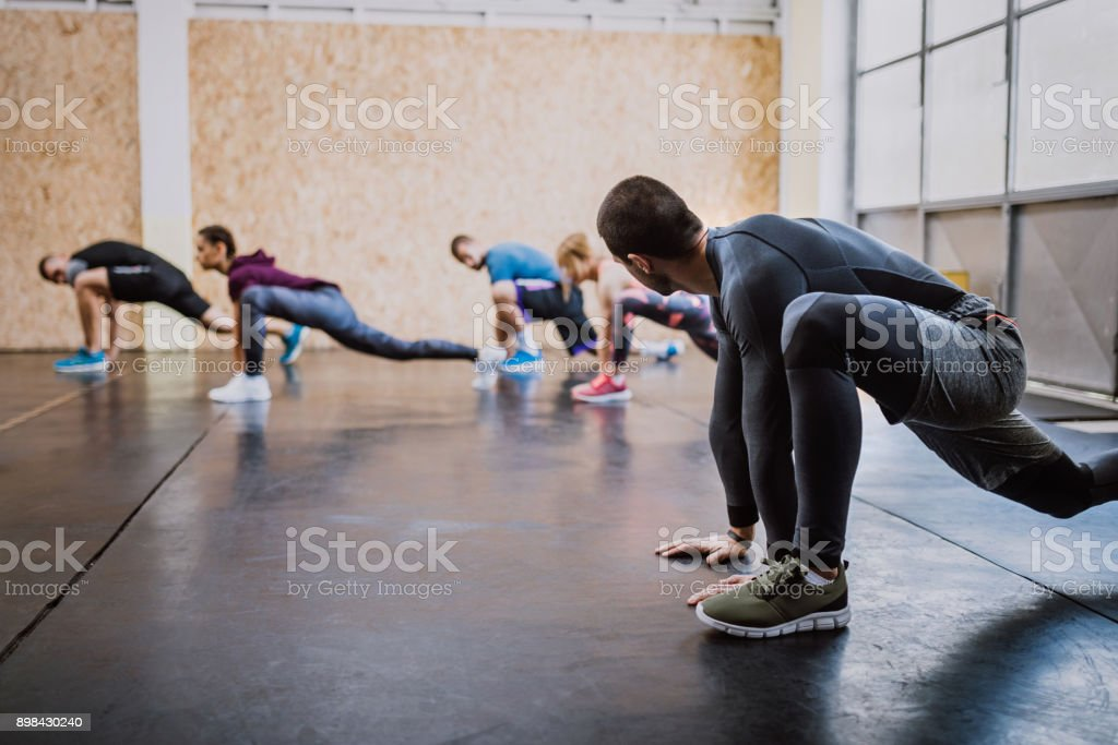 Group Of People Doing Lunges In Gym