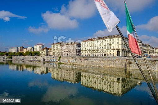 Buildings overlooking the Lungo Po Armando Diaz and the river Po, the longest river in Italy. Italian flag waving on the bridge.