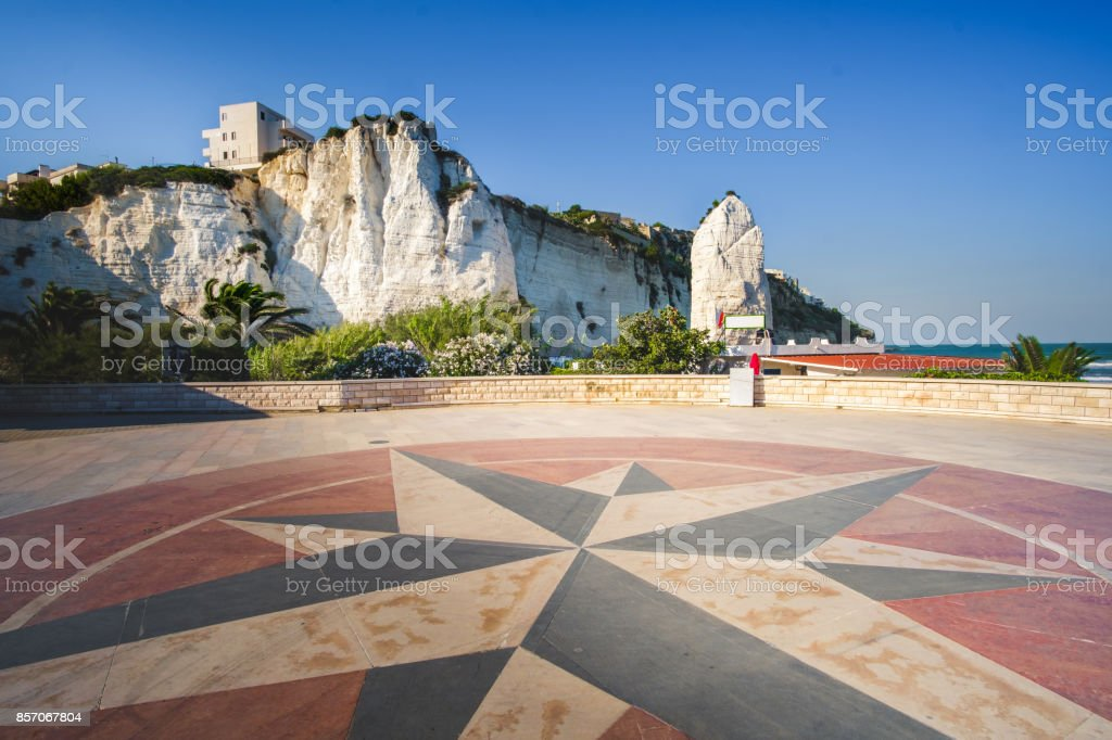 lungomare (seafront) of Vieste with a windrose symbol designed on the ground and the Pizzomunno white rock on background stock photo