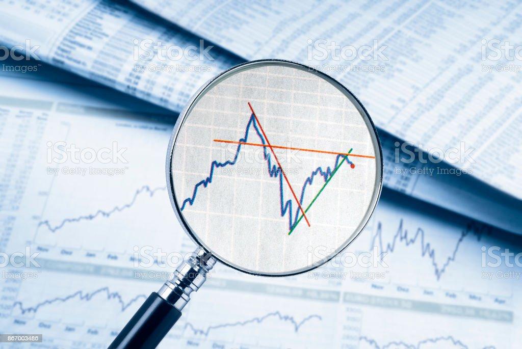 Lupe zeigt einen Aktienkurs stock photo
