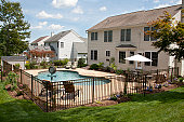 istock Lush backyard pool and patio behind colonial style home. 149477937
