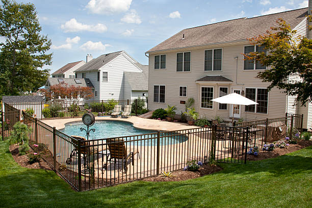 lush backyard pool and patio behind colonial style home. - fence stock photos and pictures