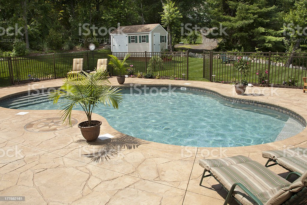 Lush backyard swimming pool and patio space. stock photo