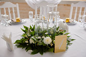 Lush floral arrangement of white chrysanthemum flowers and candles on table, copy space. Luxury wedding decorations