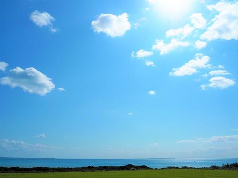 lush green field of grass and water horizon with clear blue sky background, Kohama Island, Okinawa, Japan