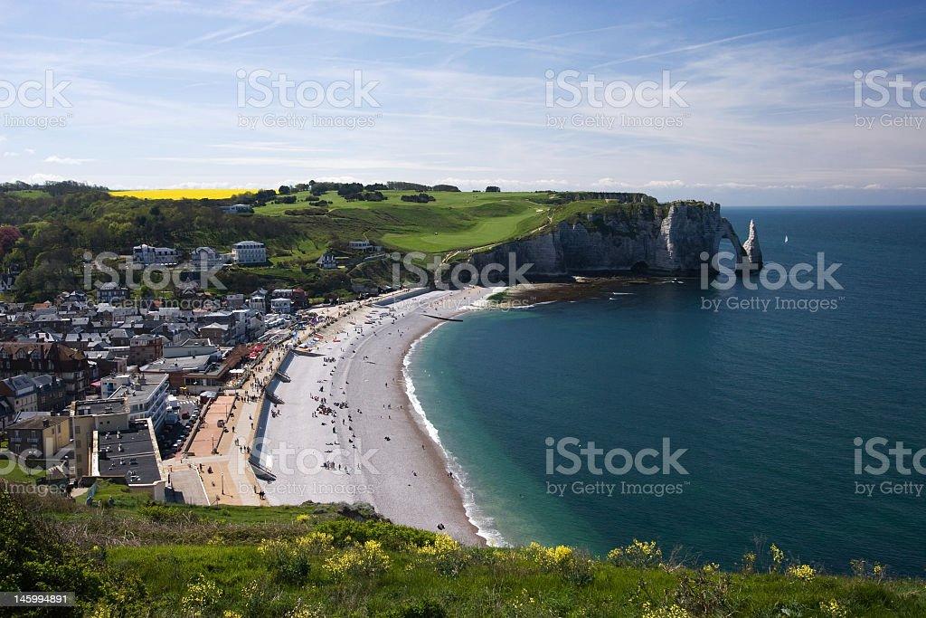 A lush green hillside overlooks a cool beach in Etretat stock photo