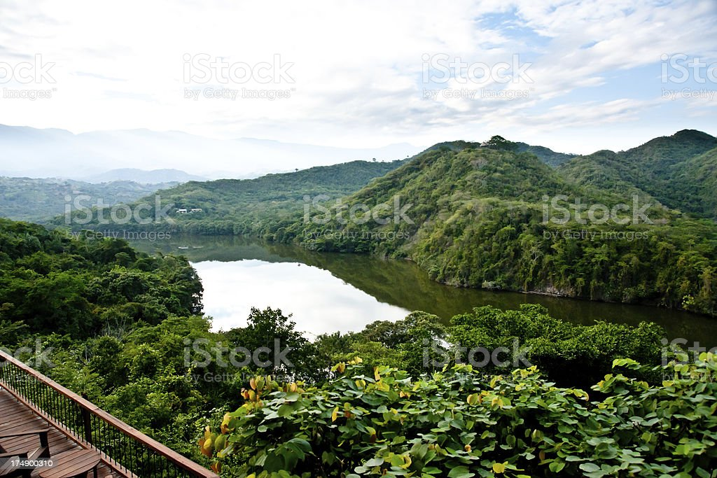 lush mountains and river in a sunny summer afternoon stock photo