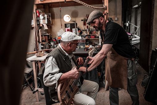 Luthier Picking Up a Guitar From Custmer's Hands After the Test.