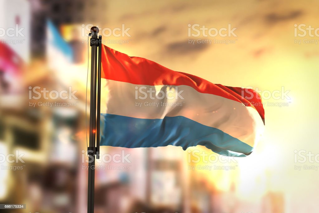 Luxembourg Flag Against City Blurred Background At Sunrise Backlight stock photo