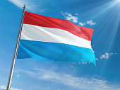 Luxembourg National Flag Waving on pole against sunny blue sky background. High Definition