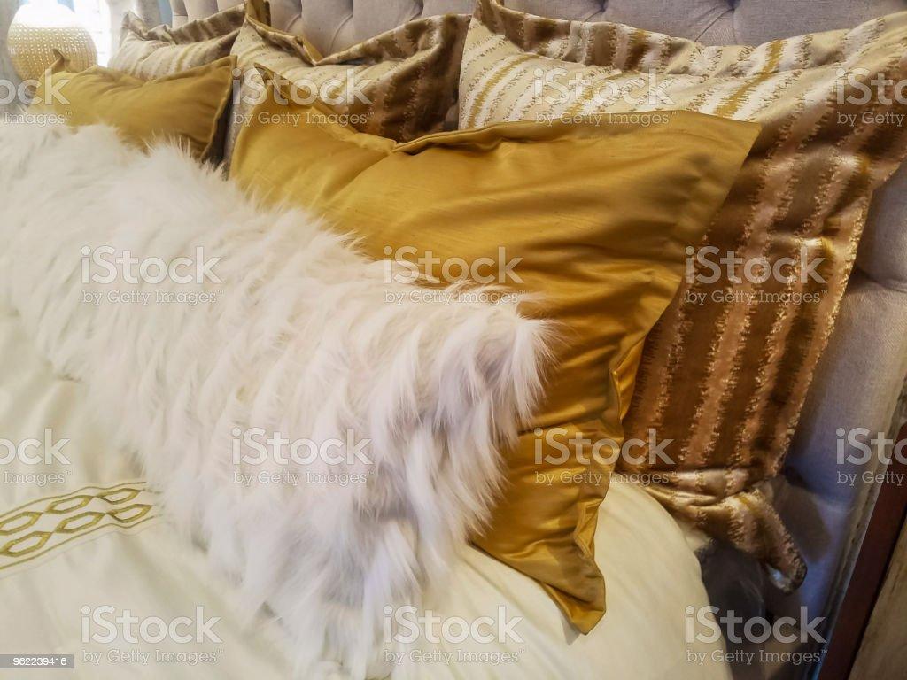 Luxiourous ouro e peles logros de descanso na cama apoiada contra beadstead acolchoado - foto de acervo