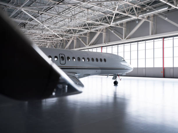 Luxorious Business Jet in Hangar Luxorious business jet plane Dassault Falcon is being stored inside the hangar airplane hangar stock pictures, royalty-free photos & images