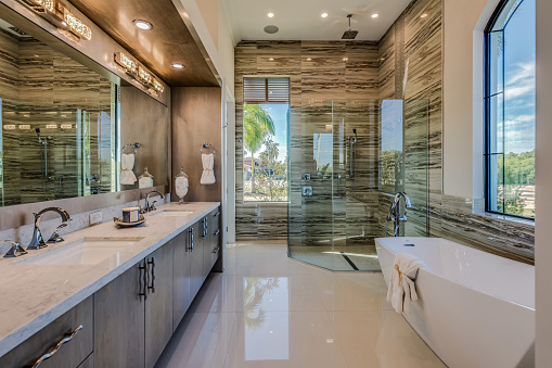 Free standing tub and big glass shower in master bathroom with amazing views