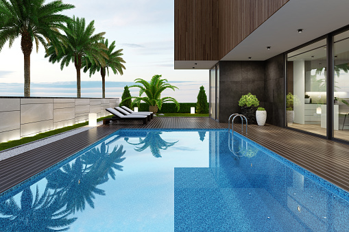 Luxurious villa with outside swimming pool at summer scene.\nBig blue swimming pool near living room and kitchen. \nStylish and comfortable sun area with a modern brown sunbeds. \nDark gray accent slate stone walls with natural plants.\nNatural floor tiles. Ceiling with white spotlights.\n\n+++ background is my photo.