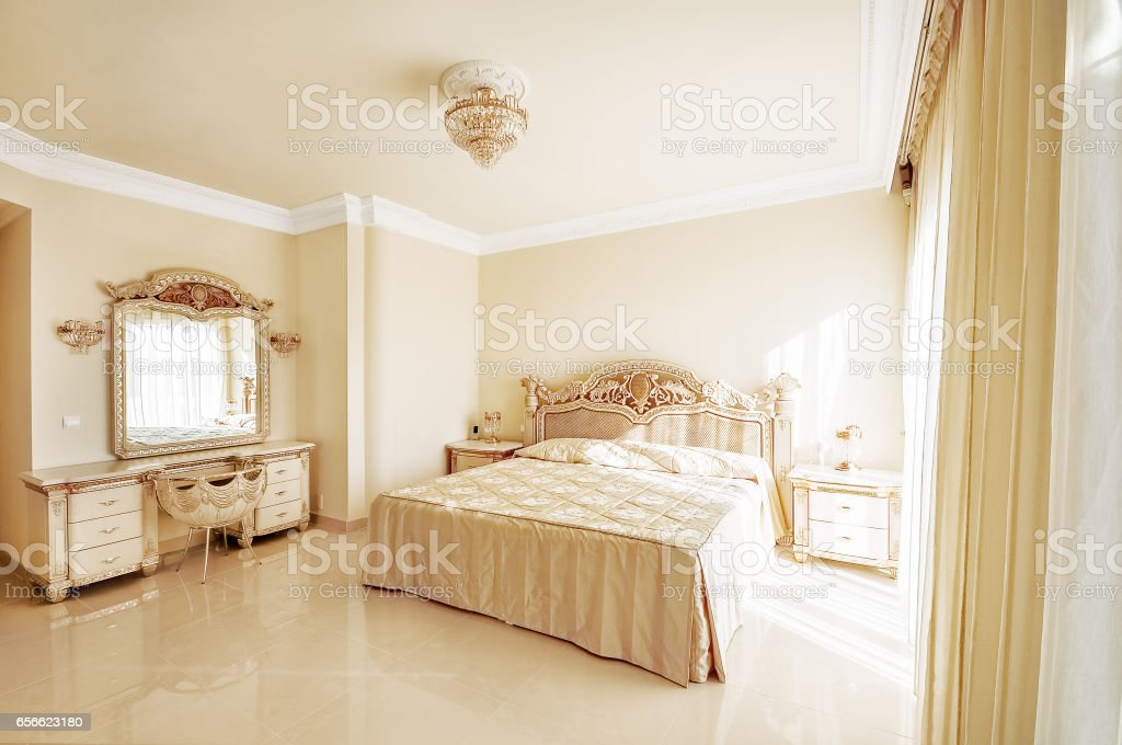 Luxurious bedroom in pastel colours in a neoclassical style, stock photo