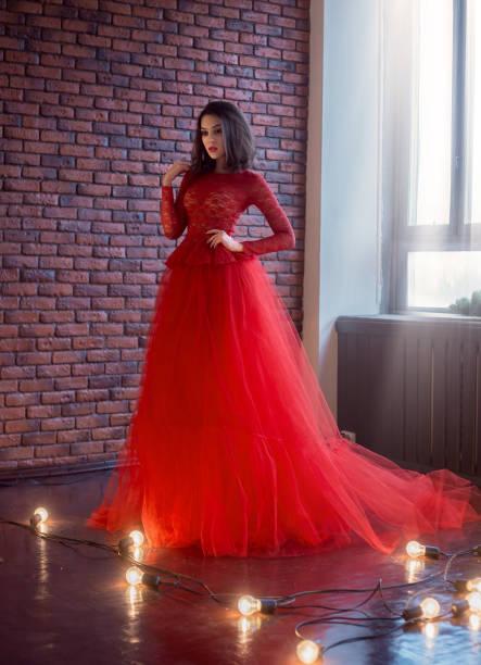 luxuriöses brünette-mädchen, mit einem bob haarschnitt, posiert in einem üppigen roten langen kleid. gotische königin vampir in einem dunklen raum. interieur im loft-minimalismus-stil. image für prom und party. - tüllkleid stock-fotos und bilder