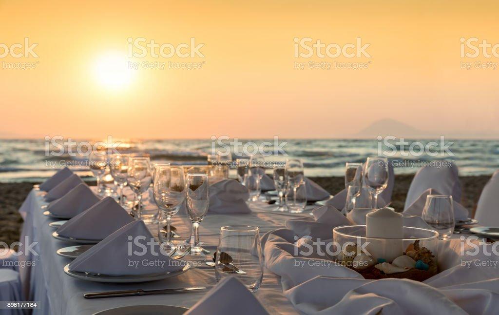 Luxurious dinner table setup on the beach stock photo