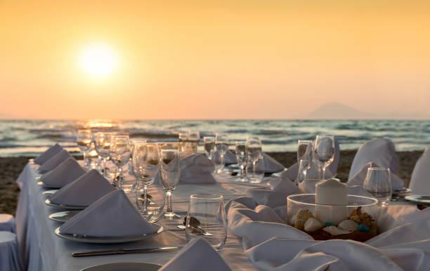 luxus esstisch setup am strand - griechische partyspeisen stock-fotos und bilder