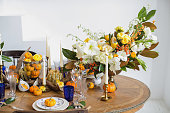 istock Luxurious elegant wedding decor in autumn style. Wooden vintage table setting with ceramic plates and silver cutlery. Fresh flowers in a vase, orange pumpkins, deer horns and candles. Romantic dinner. 1175011408