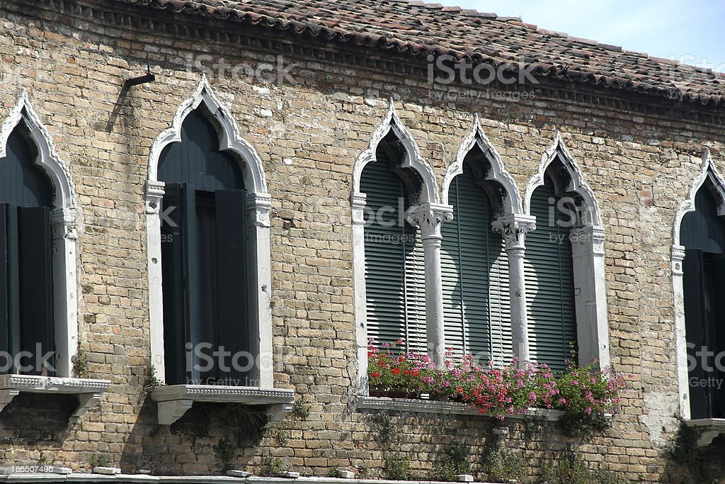 luxurious flowery balcony in Venetian style with arched windows royalty-free stock photo
