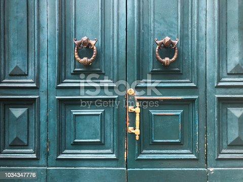 Weathered brass door knocker on teal painted double door in Paris France.