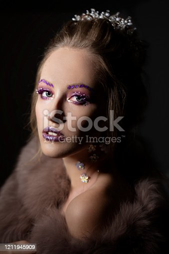 Luxurious girl with a beautiful make-up in a fur coat. Beauty in furs. Model on a dark background. Young beautiful woman.
