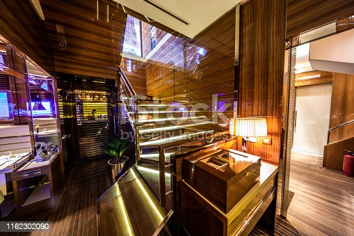 An illuminated, high shine staircase made of tick wood in a classy restaurant. A box of cigars is located at the bottom area of the staircase.