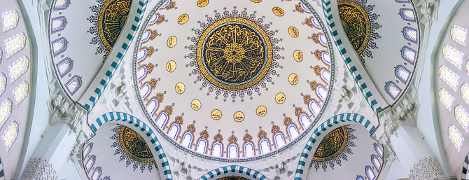 Ankara, Turkey - June 14, 2021: magnificent interior of a new mosque Hatun Camii in Ankara, Turkey. Arched vaults, domes and light marble walls. Famous place of worship and tourist attraction. Muslim culture of the Middle East. Travel and Tourism