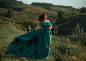 Luxurious lady in long green dress with bare shoulders.
