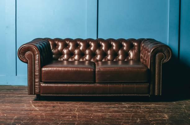 luxuriöse leder, braun sofa, blaue wand. klassische vintage-möbel. - ledersessel braun stock-fotos und bilder