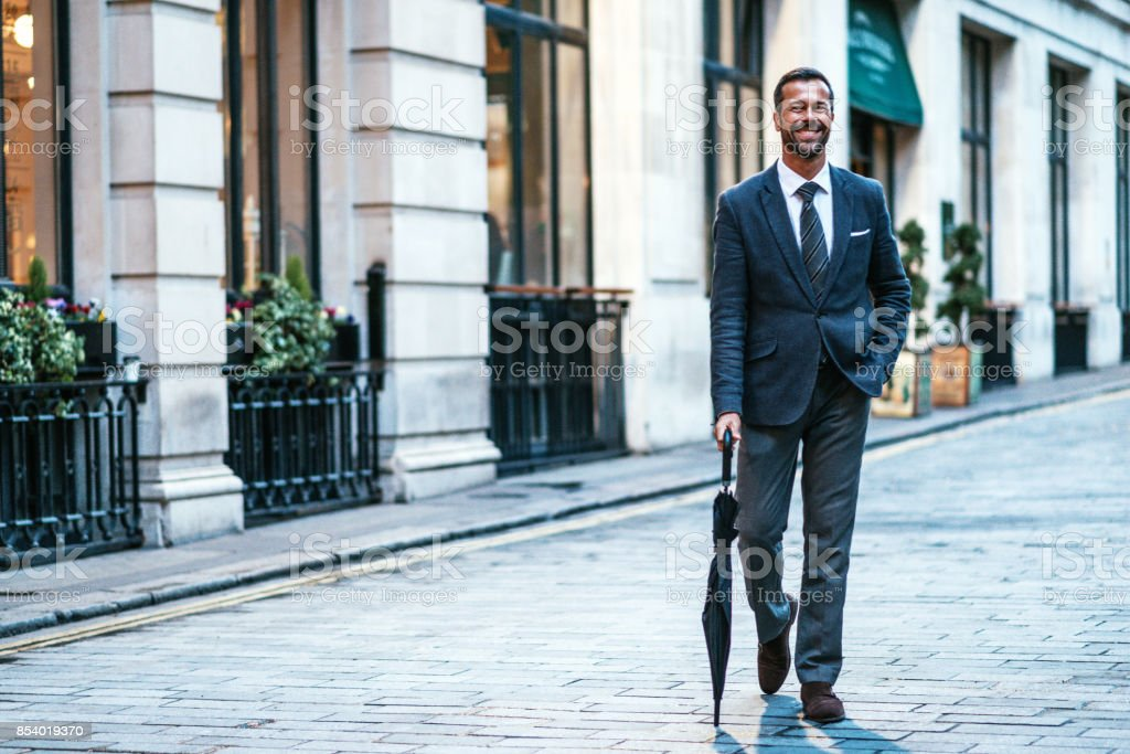 Luxurious living in London - gentleman with umbrella near his restaurant stock photo