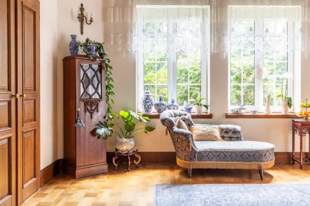 A luxurious living room interior with a couch and a wooden cabinet standing on a parquet against two large windows. Real photo. A luxurious living room interior with a couch and a wooden cabinet standing on a parquet against two large windows. Real photo. tradition stock pictures, royalty-free photos & images