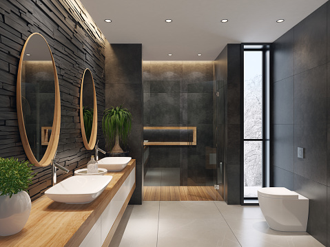 contemporary minimalist bathroom with two round mirrors and wooden frame. natural stacked black matte stone wall with large black matte tiles. two rectangular white wash basins are on top of the long wooden cabinet with white doors. large white matte floor tiles. wooden floor tiles in walk-in shower. ceiling strip cove lighting with embedded spotlights.