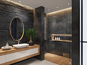 contemporary minimalist bathroom with two round mirrors and wooden frame.\nnatural stacked black matte stone wall with large black matte tiles.\ntwo rectangular white wash basins are on top of the long wooden cabinet with\nwhite doors. large white matte floor tiles. wooden floor tiles in walk-in shower.\nceiling strip cove lighting with embedded spotlights.