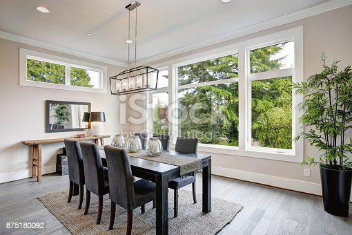 Luxurious modern dining room boasts a black dining table illuminated by a rectangular chandelier and surrounded by gray velvet dining chairs over taupe sisal rug finished with rustic console table.