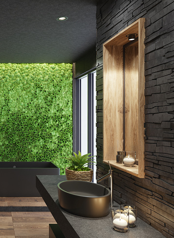 Trendy and modern home spa bathroom with matte black tiles, black stacked stone wall and lots of natural light. Green moss plant wall for cozy interior. Modern black bath tub. Wooden tiles on some walls. Candles light. Big panoramic windows. Nature wood texture stone floor. 3d rendering.