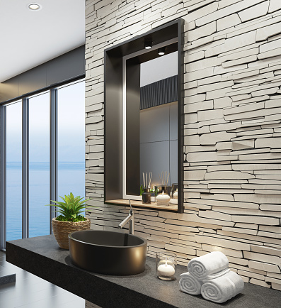 Trendy and modern home spa bathroom with matte black tiles, white stacked stone wall and lots of natural light. Cozy interior. Modern black bath tub and sink. Black and white concept. Candles light. Big panoramic windows. Black stone floor. 3d rendering.  +++background is my photo