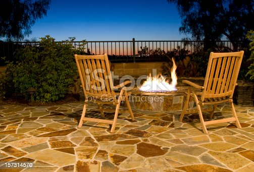 Twilight view of a back yard with fire pit.